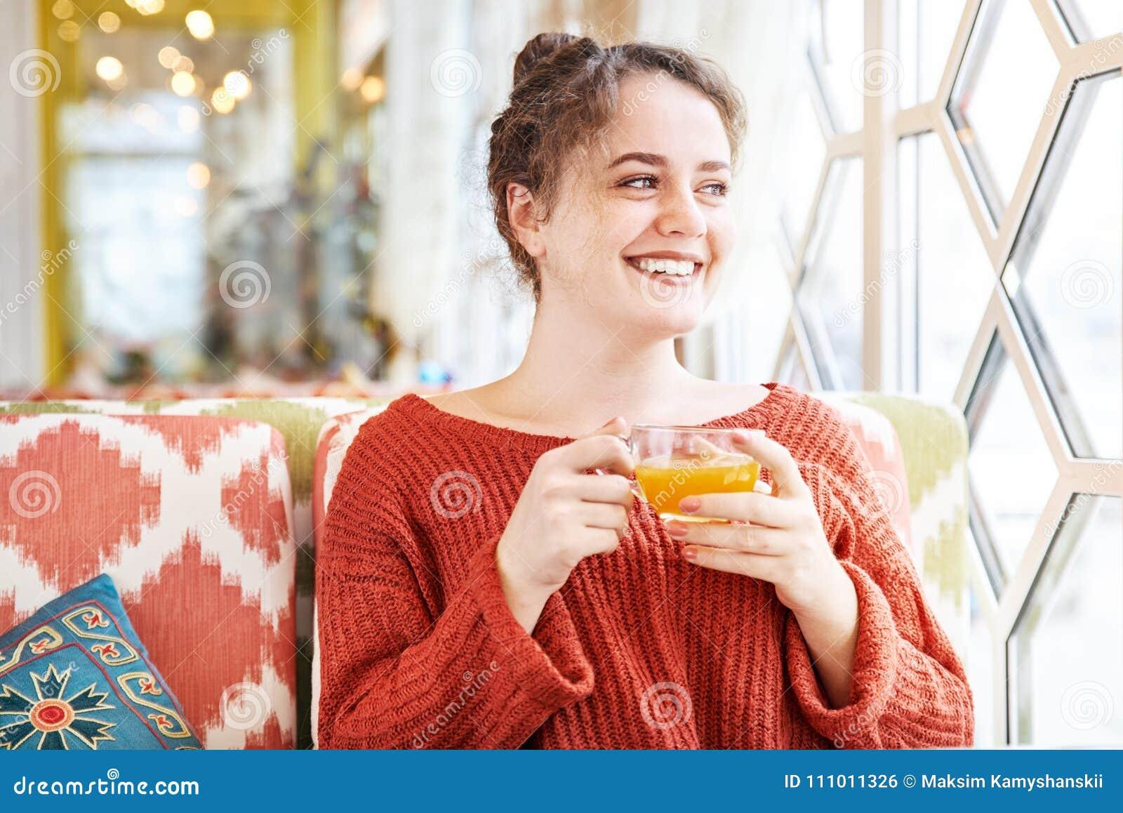 Lycklig skratta ung rödhårig mankvinna som har frukosten i ett kafé tidigt på morgonen med en kopp