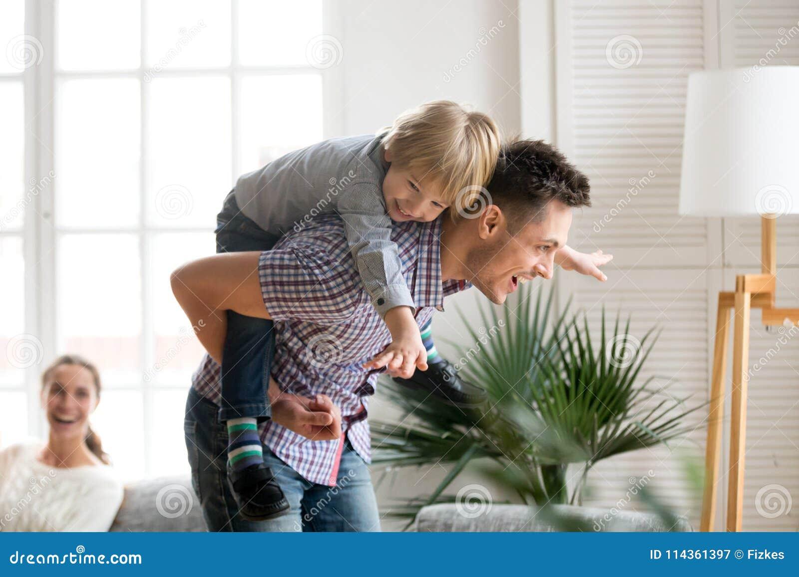 Lycklig son för farsainnehavunge på baksida som på ryggen ger ritt