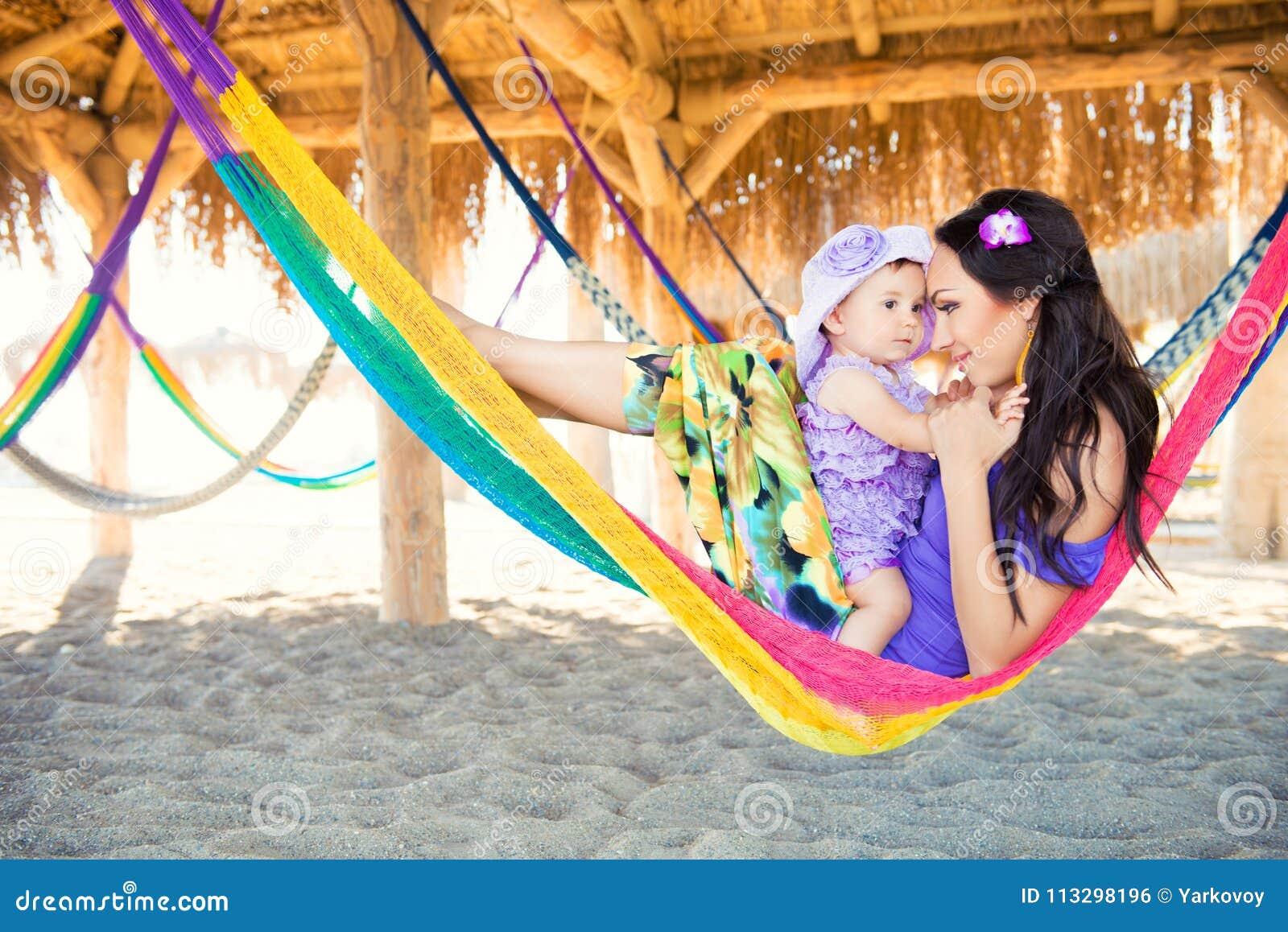 Lycklig stilfull familj med den gulliga dottern som kopplar av i hängmatta på sommarsemester i aftonsolljus på stranden hipsterpa