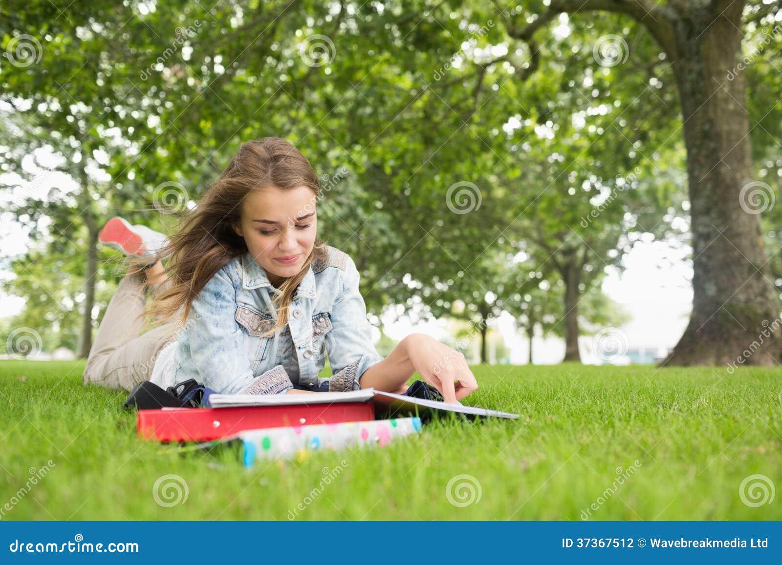 Lycklig student som ligger på studera för gräs
