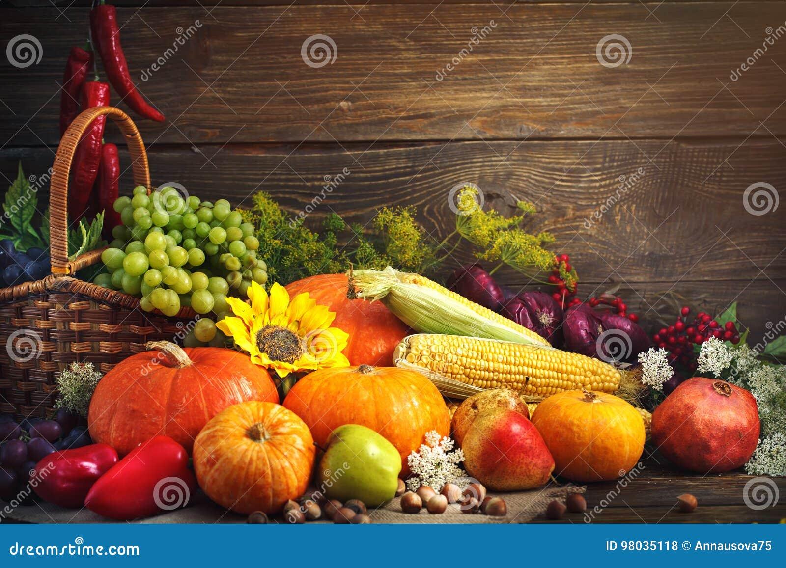 Lycklig tacksägelsedagbakgrund, trätabell som dekoreras med pumpor, majs, frukter och höstsidor