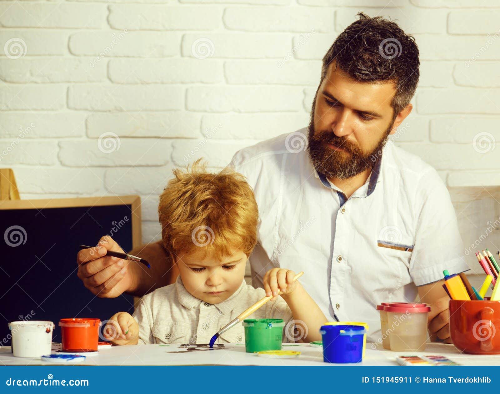 Lycklig tid f?r familj Konst med fadern Farsa och son som tillsammans m?lar Tajma till skolar Konstutbildning