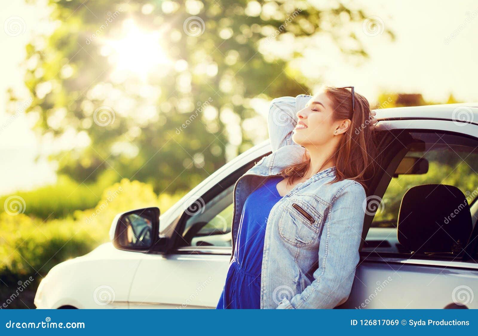 Lycklig tonårs- flicka eller ung kvinna i bil