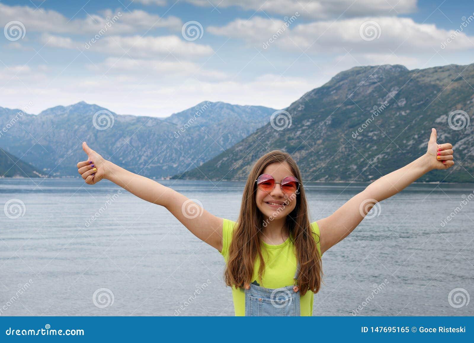 Lycklig tonårs- flicka med tummar upp på den Kotor för sommarsemester fjärden