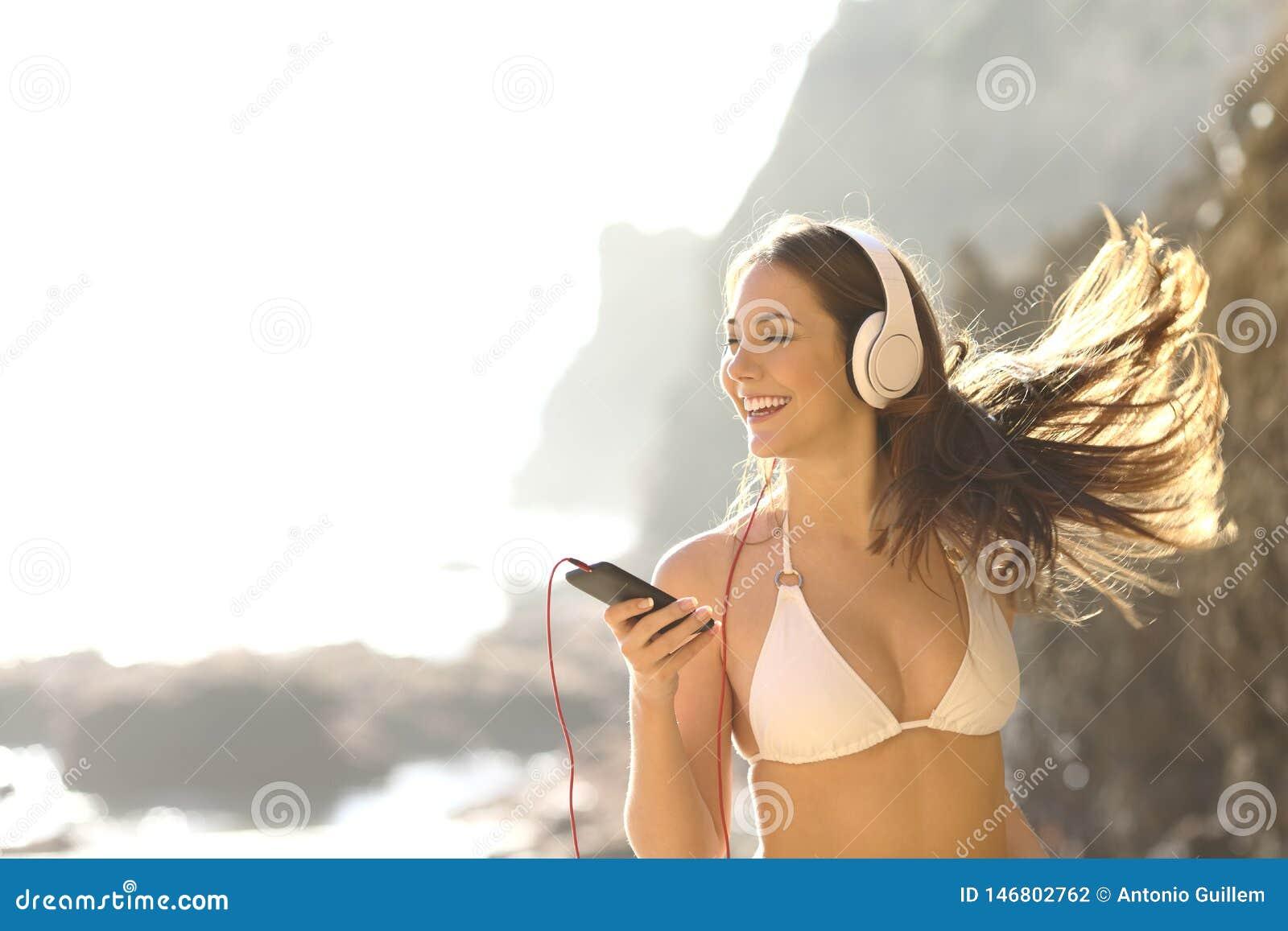 Lycklig turist i bikini som lyssnar till musik på semester
