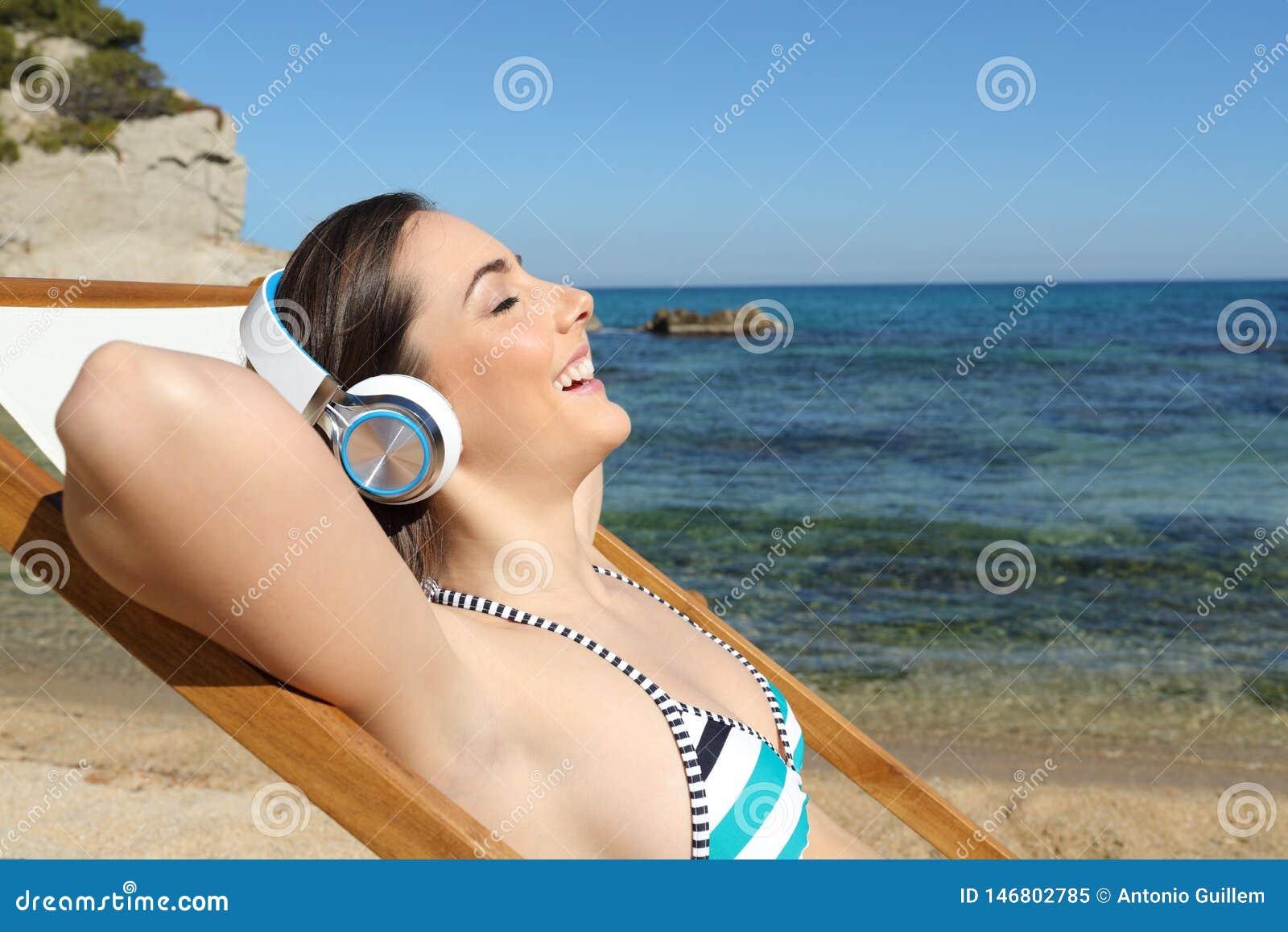 Lycklig turist som lyssnar till musik som kopplar av på stranden