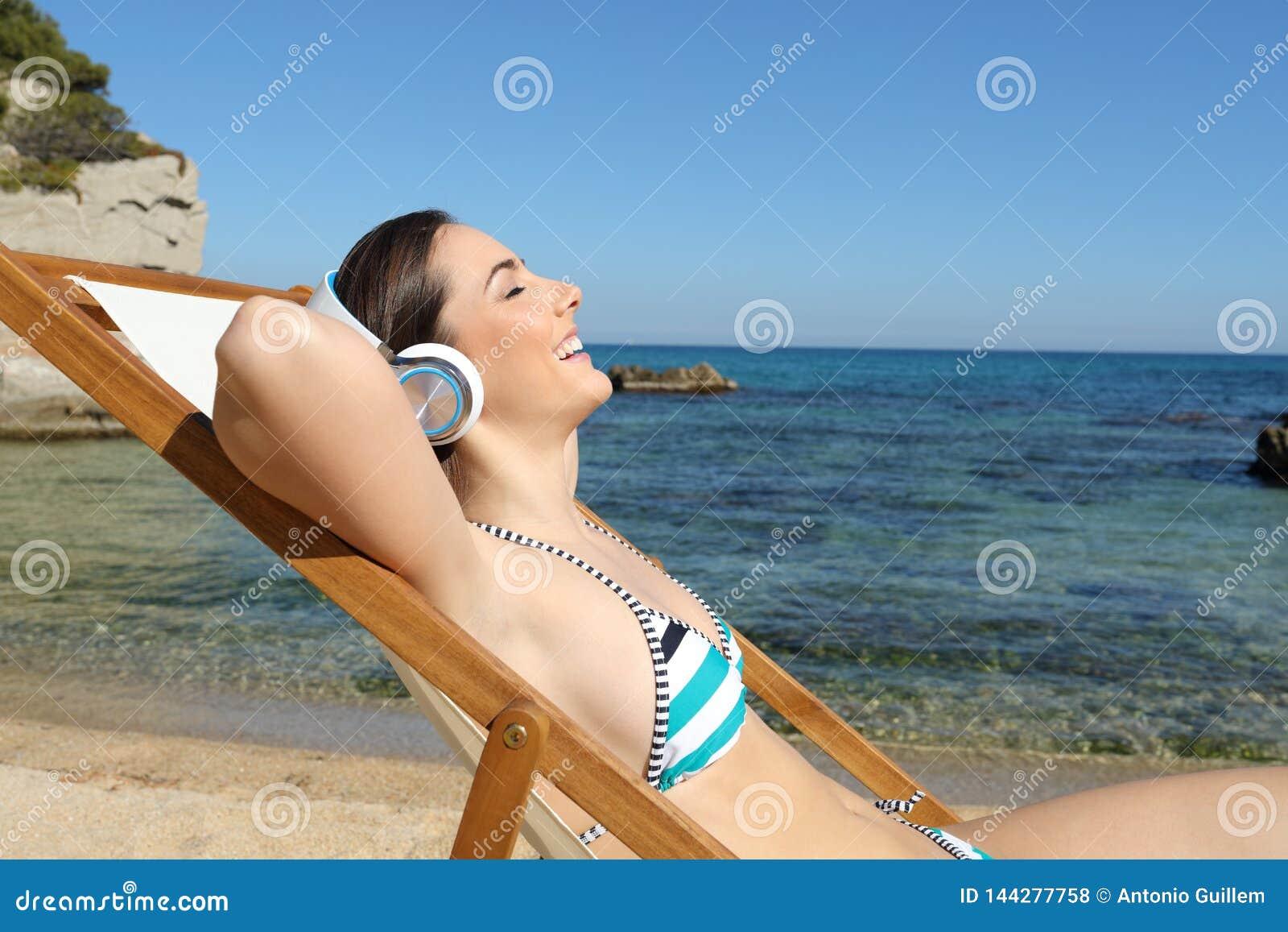 Lycklig turist som lyssnar till musik som vilar på stranden