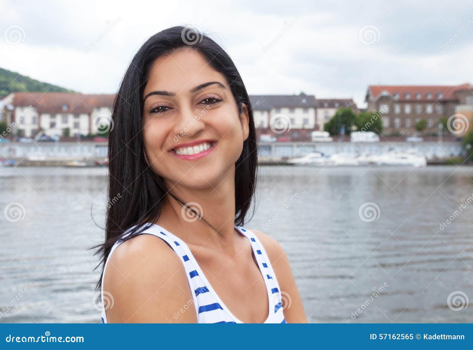 Lycklig turkisk kvinna i en randig skjorta utanför