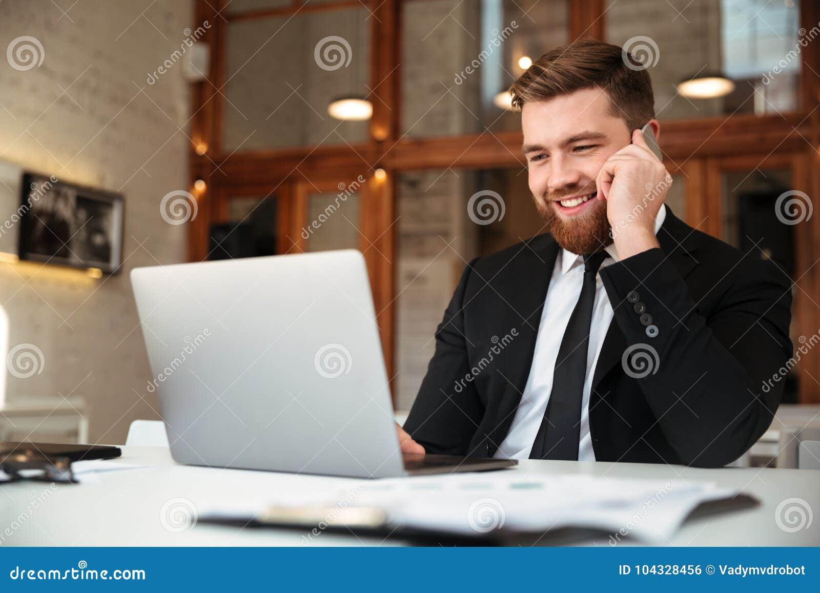 Lycklig ung affärsman i svart dräkt som talar på mobiltelefon, l