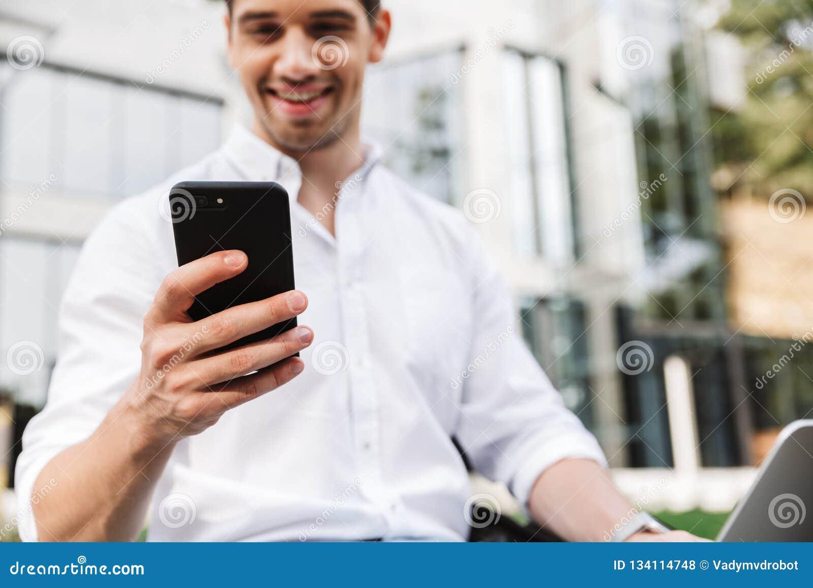 Lycklig ung affärsman som använder mobiltelefonen
