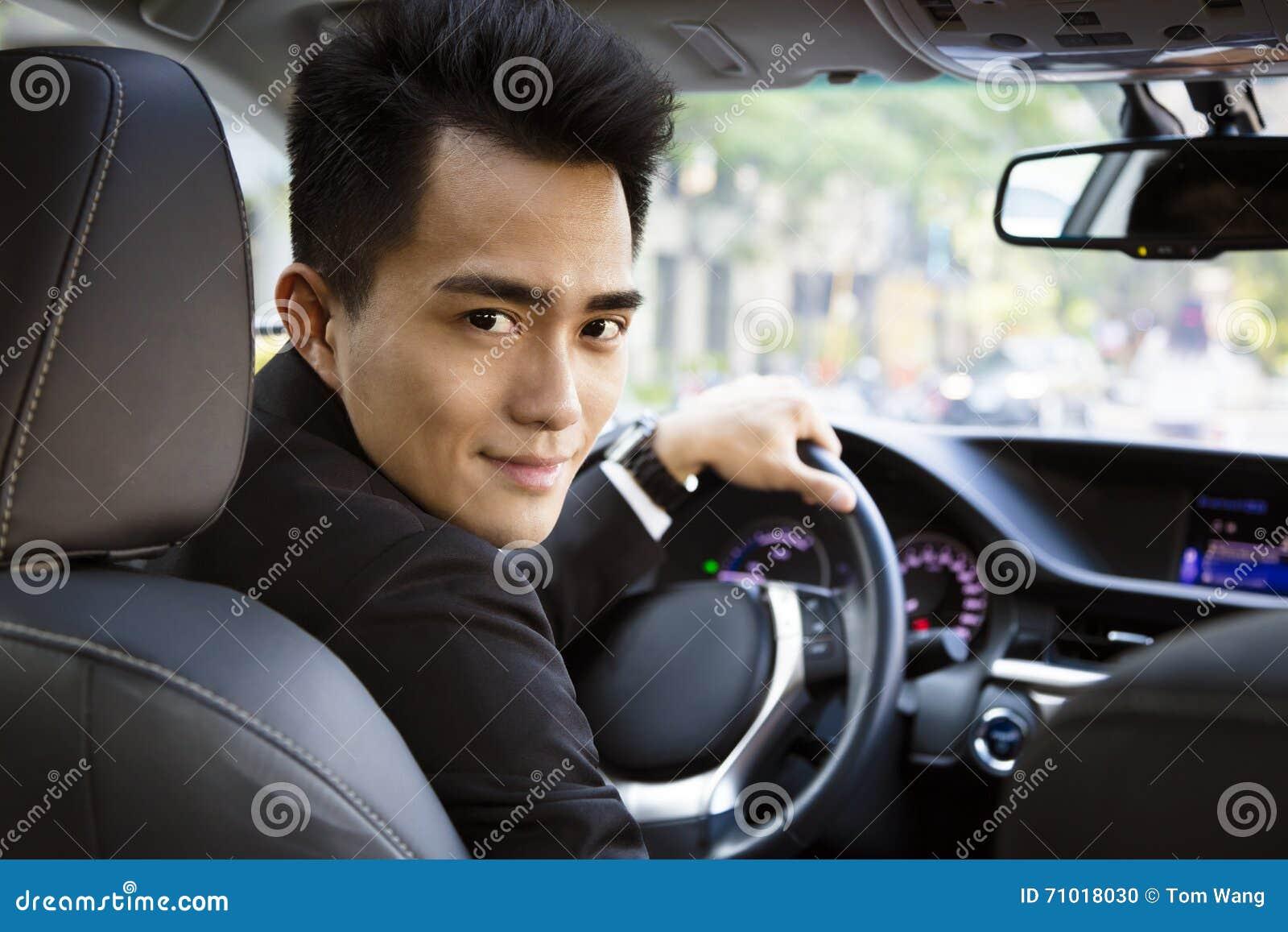 Lycklig ung affärsman som kör i bilen