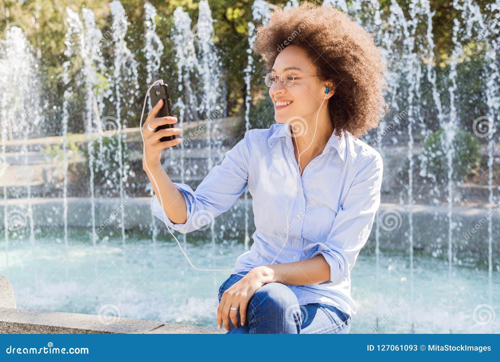 Lycklig ung afrikansk amerikankvinna i tillfälliga kläder, genom att använda Smartphones för socialt nätverk
