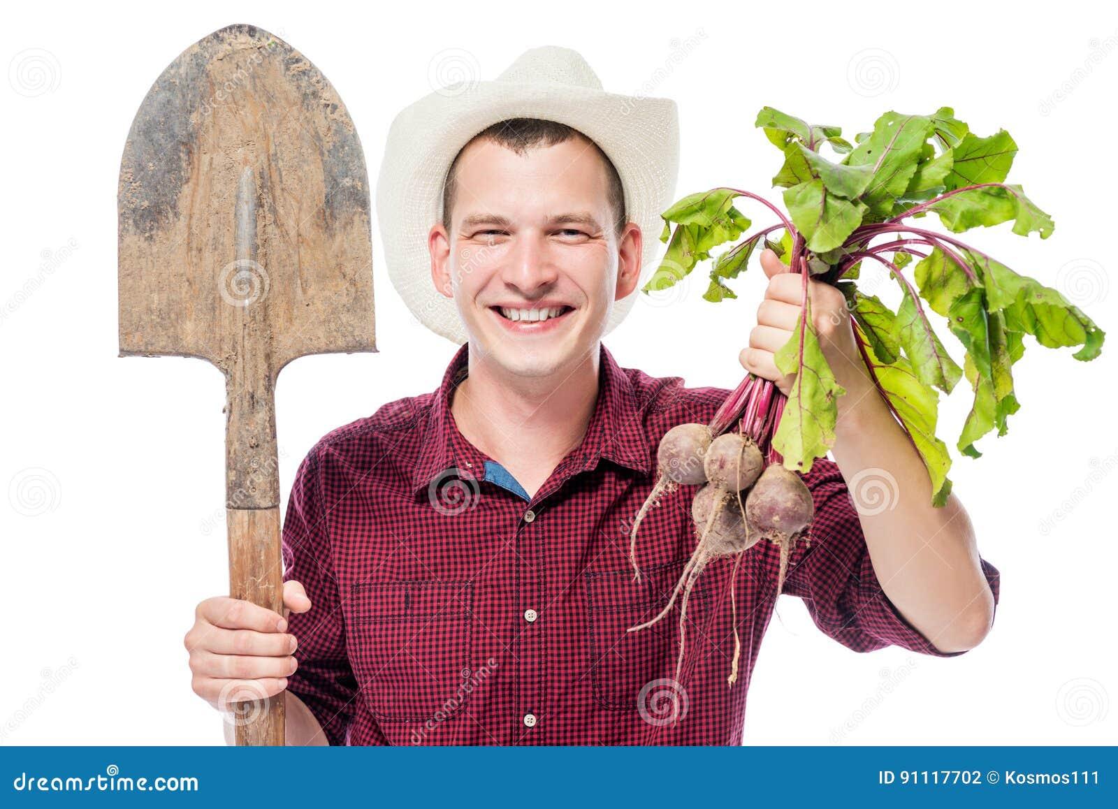 Lycklig ung bonde i en hatt med en betaskörd på en vit