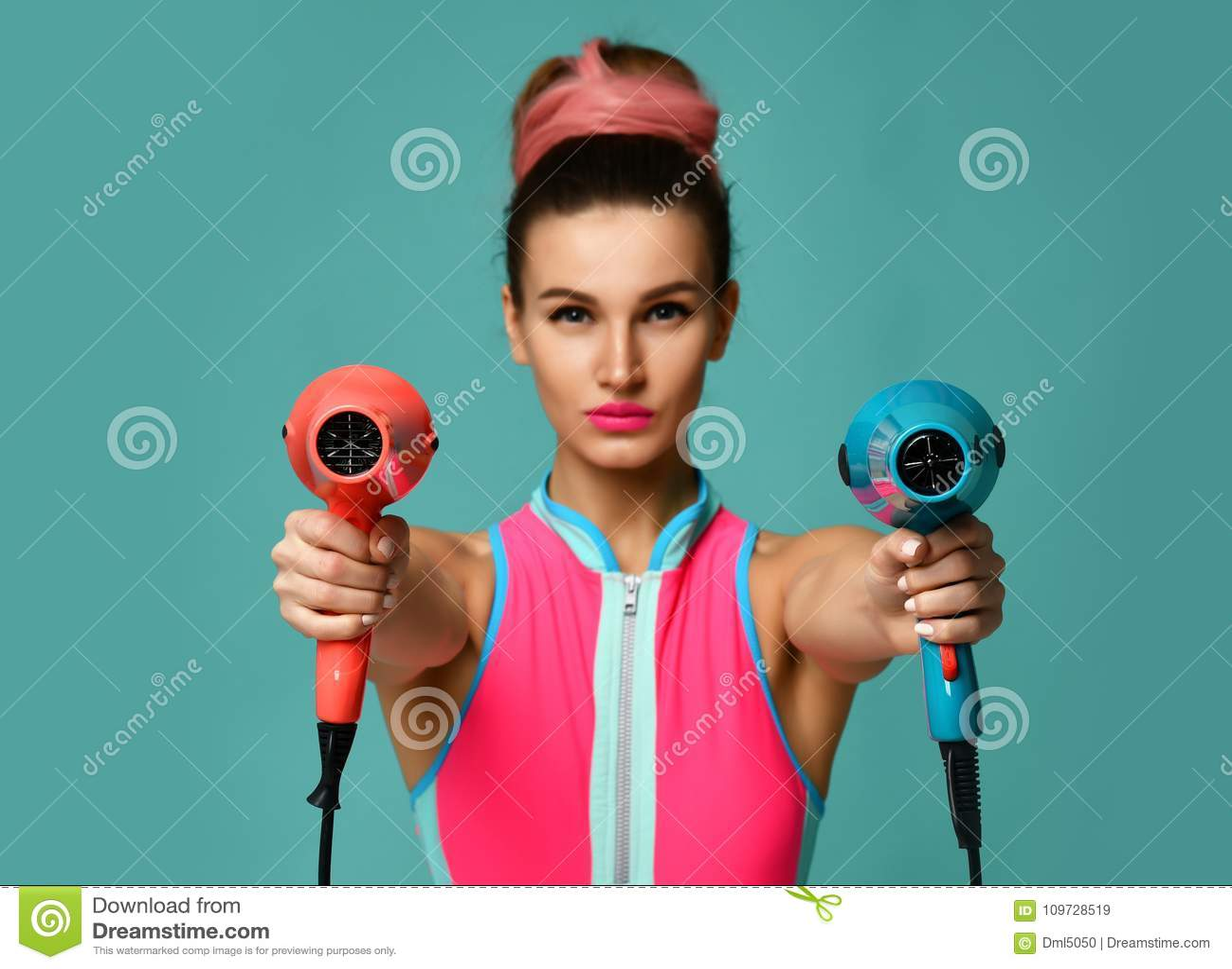 Lycklig ung brunettkvinna med hårtorken på blå mintkaramellbakgrund