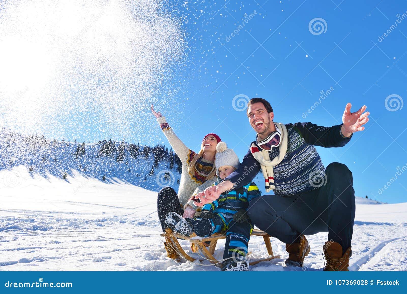 Lycklig ung familj som spelar i ny snö på härliga soliga den utomhus- vinterdagen i natur