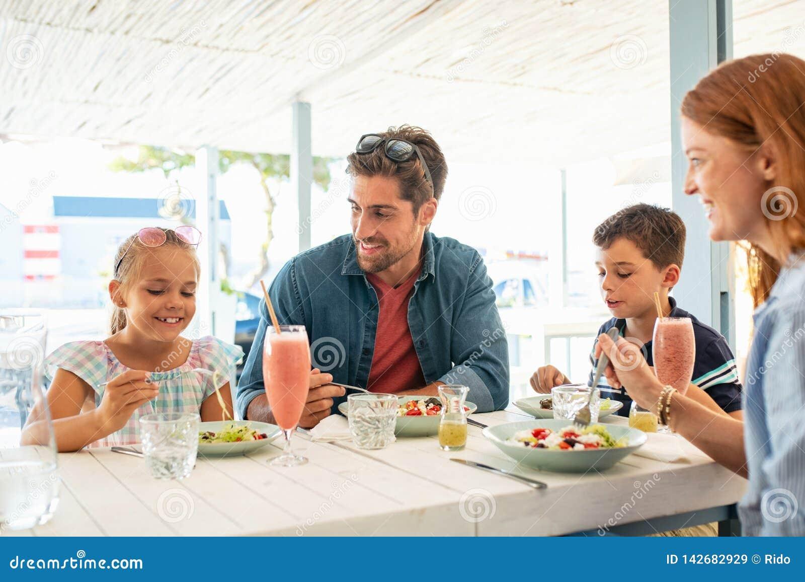 Lycklig ung familj som tycker om utomhus- lunch