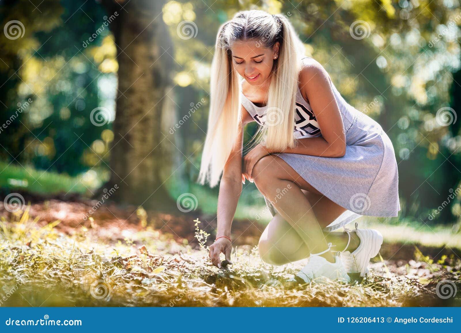 Lycklig ung flicka i en äng som upp väljer något från jordningen Med den bundna grå färgklänningen och blont hår