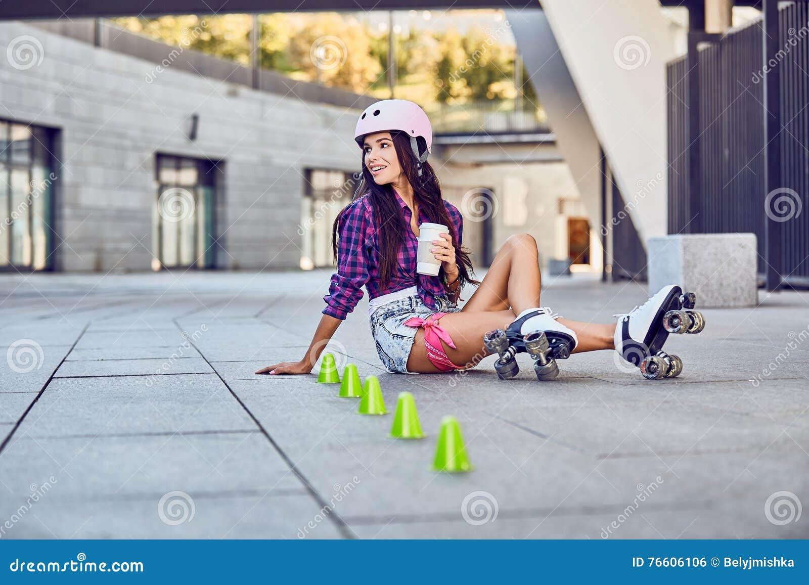 Lycklig ung flicka som tycker om rullen som åker skridskor med kaffe