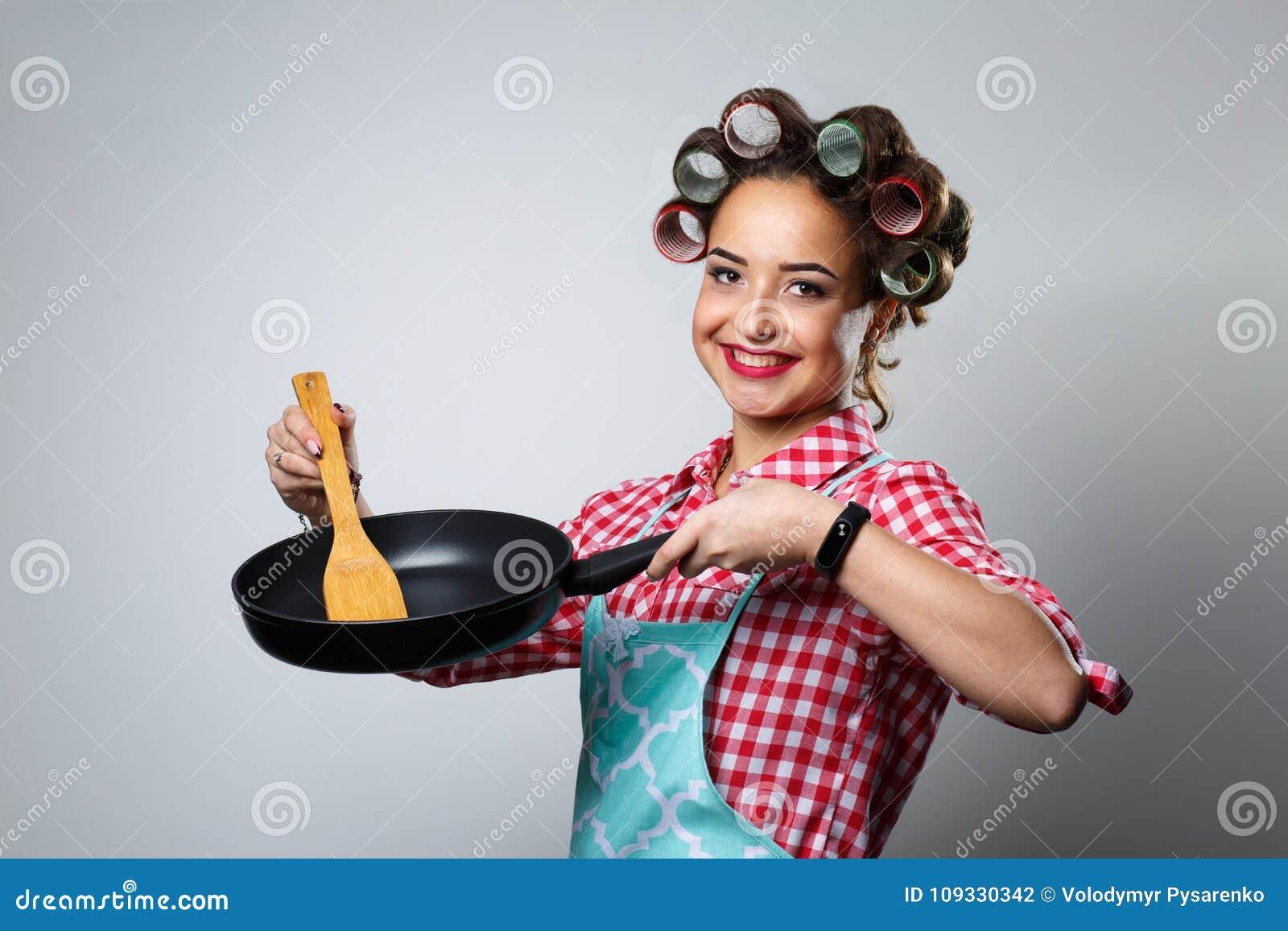 Lycklig ung hemmafru med en stekpanna på en grå bakgrund