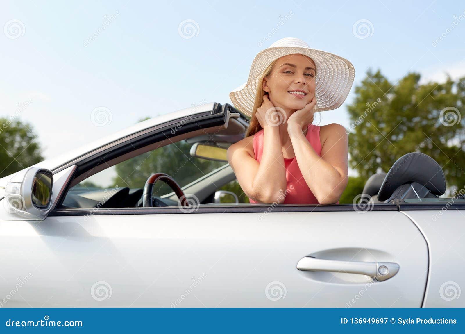 Lycklig ung kvinna i konvertibel bil