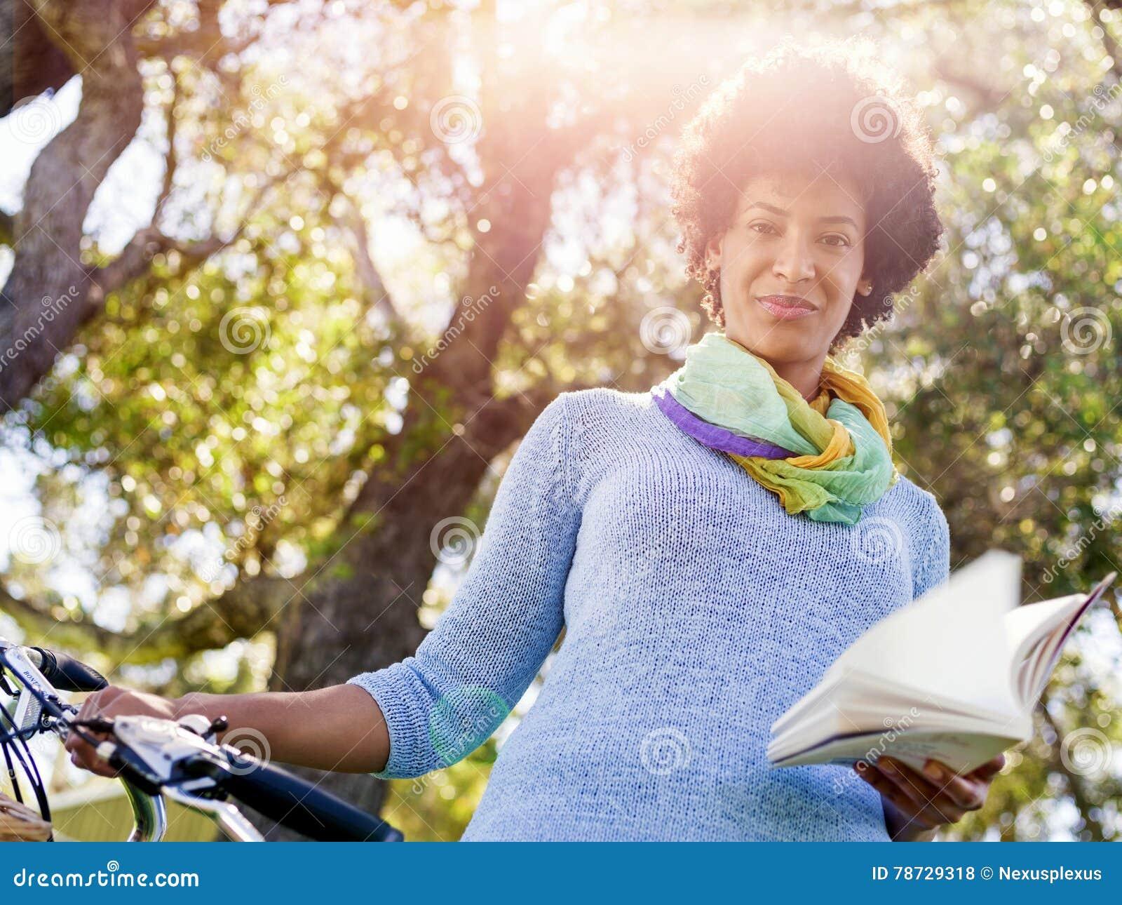 Lycklig ung kvinna med cykelläseboken