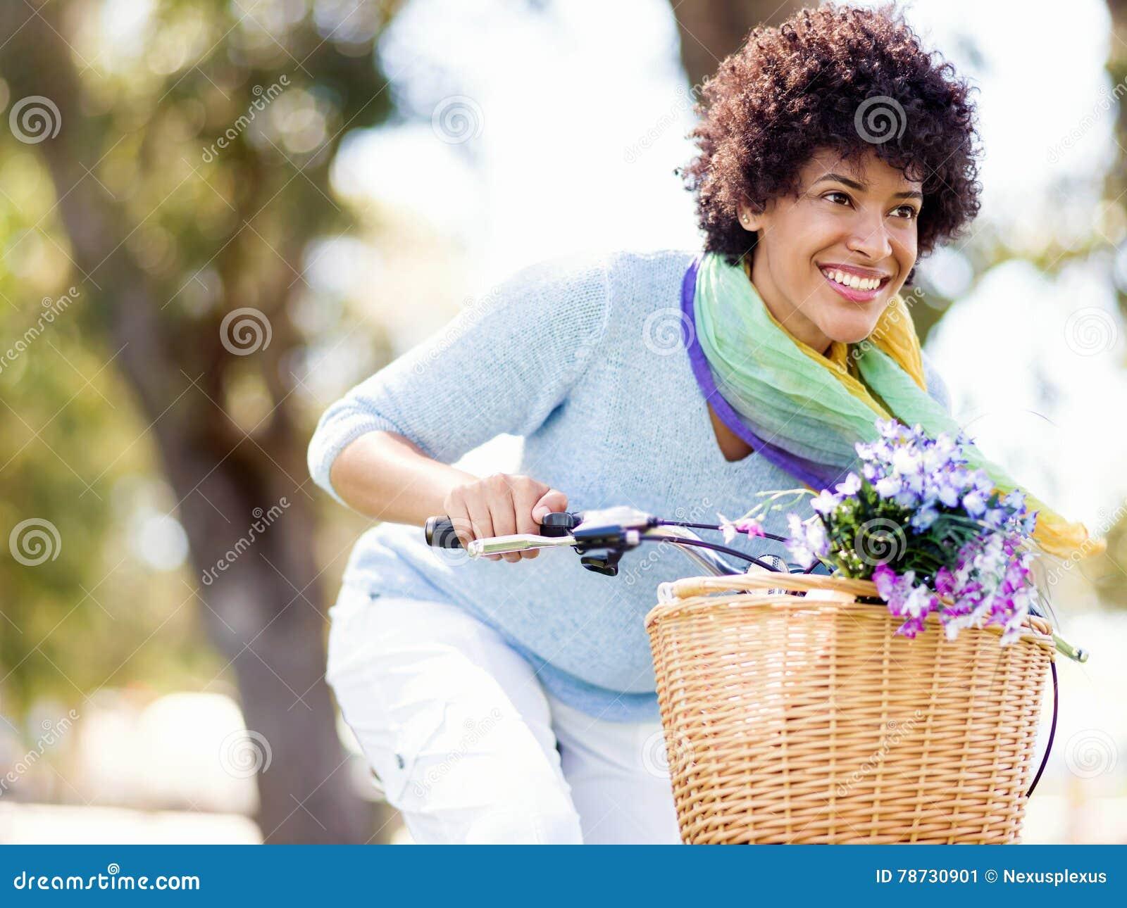 Lycklig ung kvinna med cykeln
