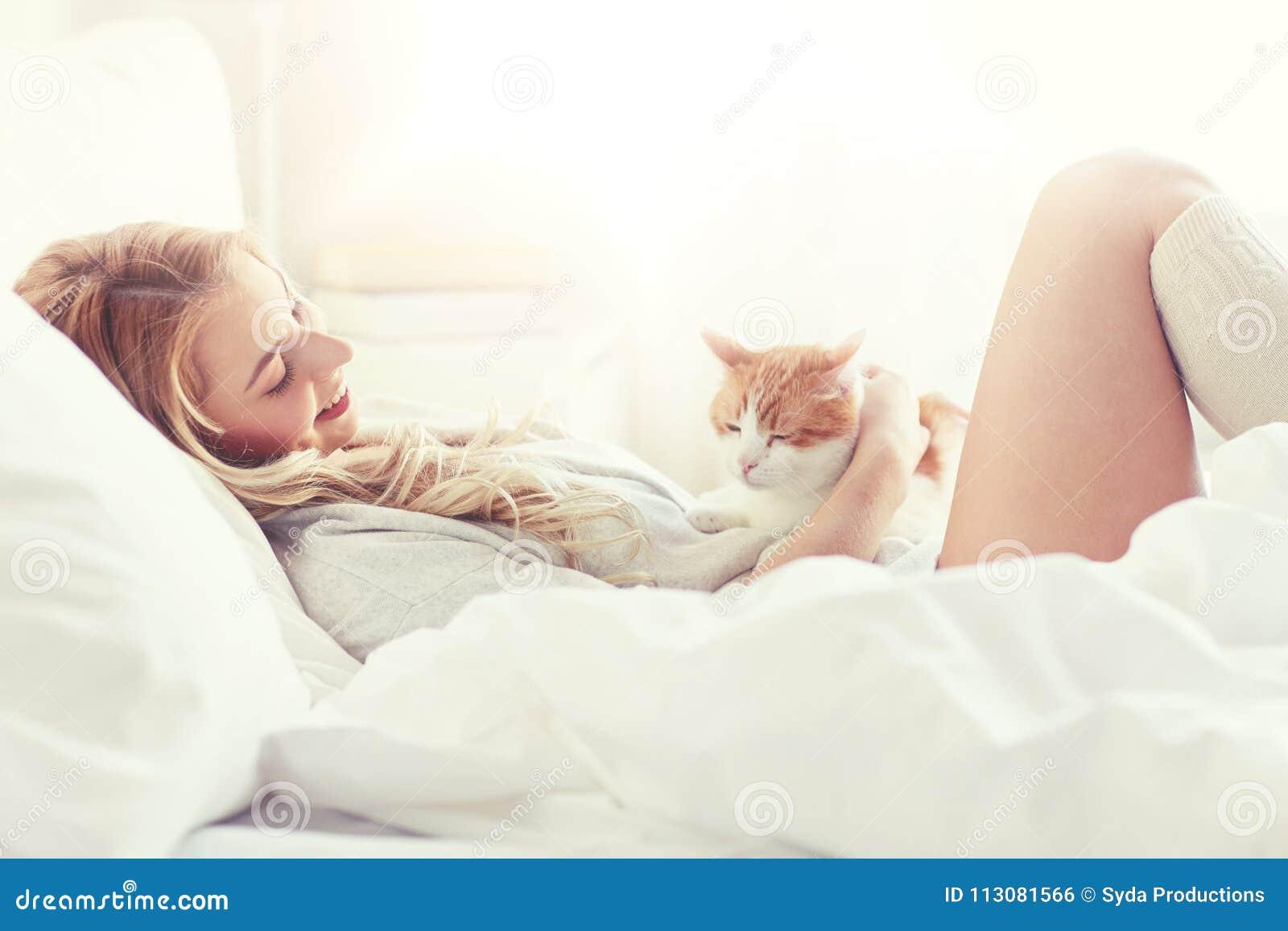 Lycklig ung kvinna med katten i säng hemma