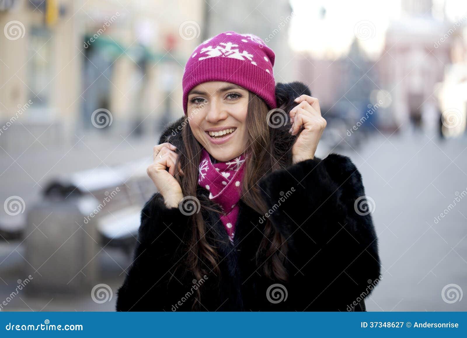 Lycklig ung kvinna på en bakgrund av en vinterstad