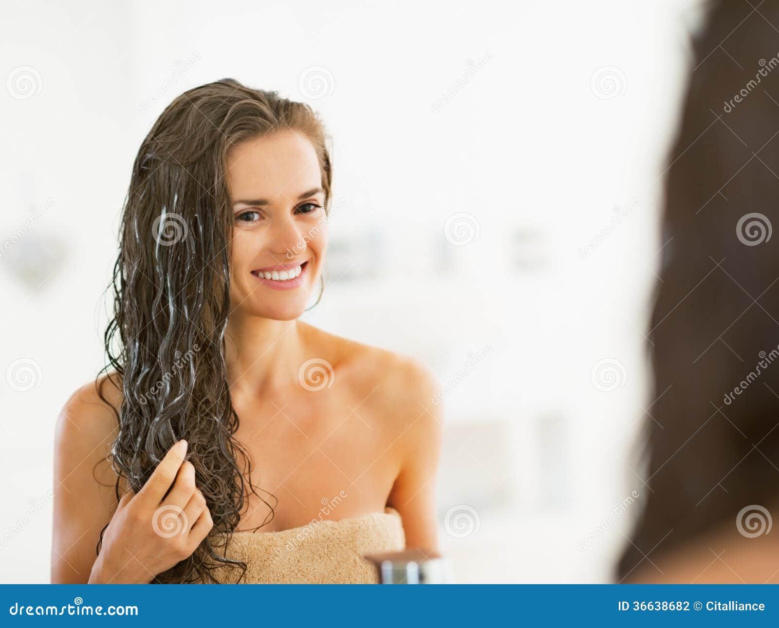 Lycklig ung kvinna som applicerar hårmaskeringen i badrum