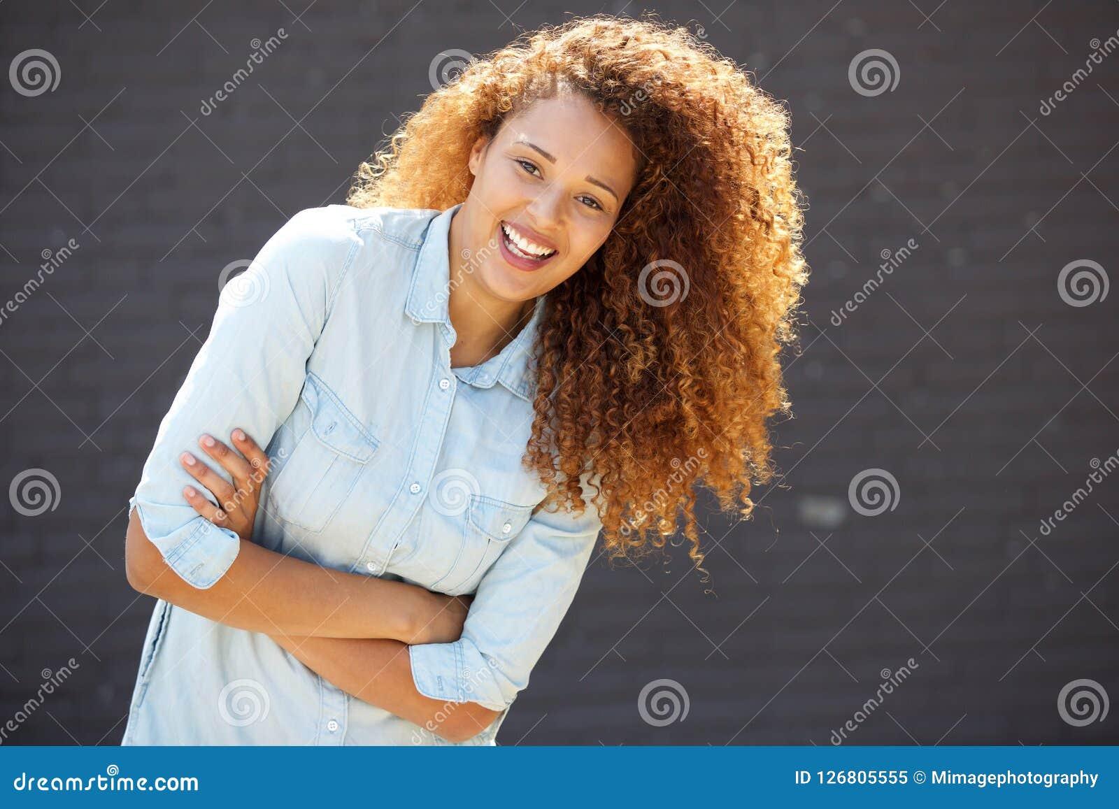 Lycklig ung kvinna som ler med armar som korsas av den gråa väggen