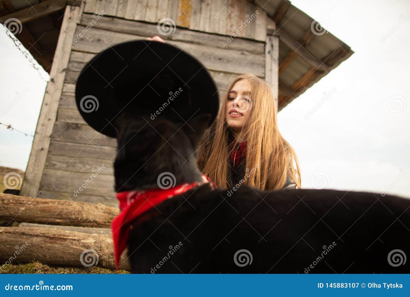 Lycklig ung kvinna som plaing med hennes svarta hund i fron av det gamla tr?huset Flickan f?rs?ker en hatt till hennes hund