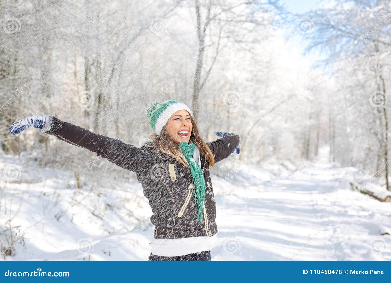 Lycklig ung kvinna som spelar i snön