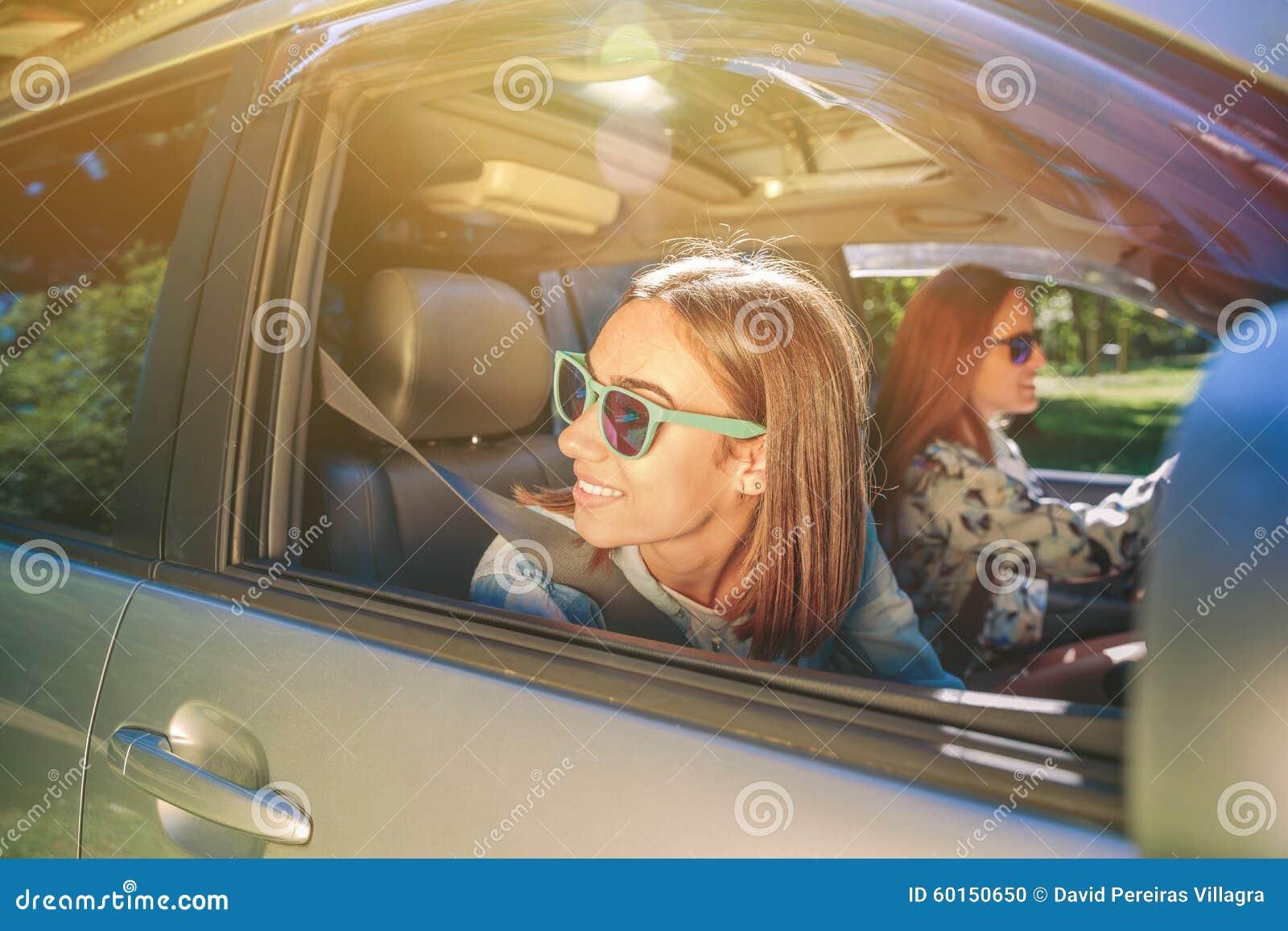 Lycklig ung kvinna som tillbaka ser till och med fönstret