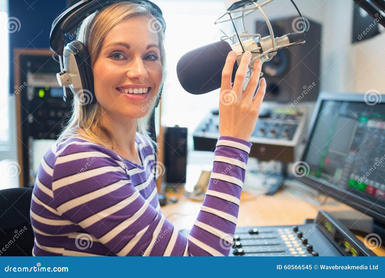 Lycklig ung kvinnlig radiovärdsradioutsändning i studio