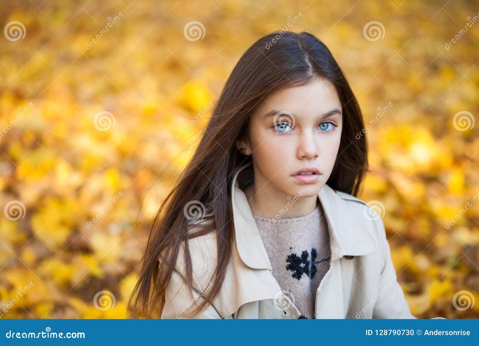 Lycklig ung liten flicka i beige lag
