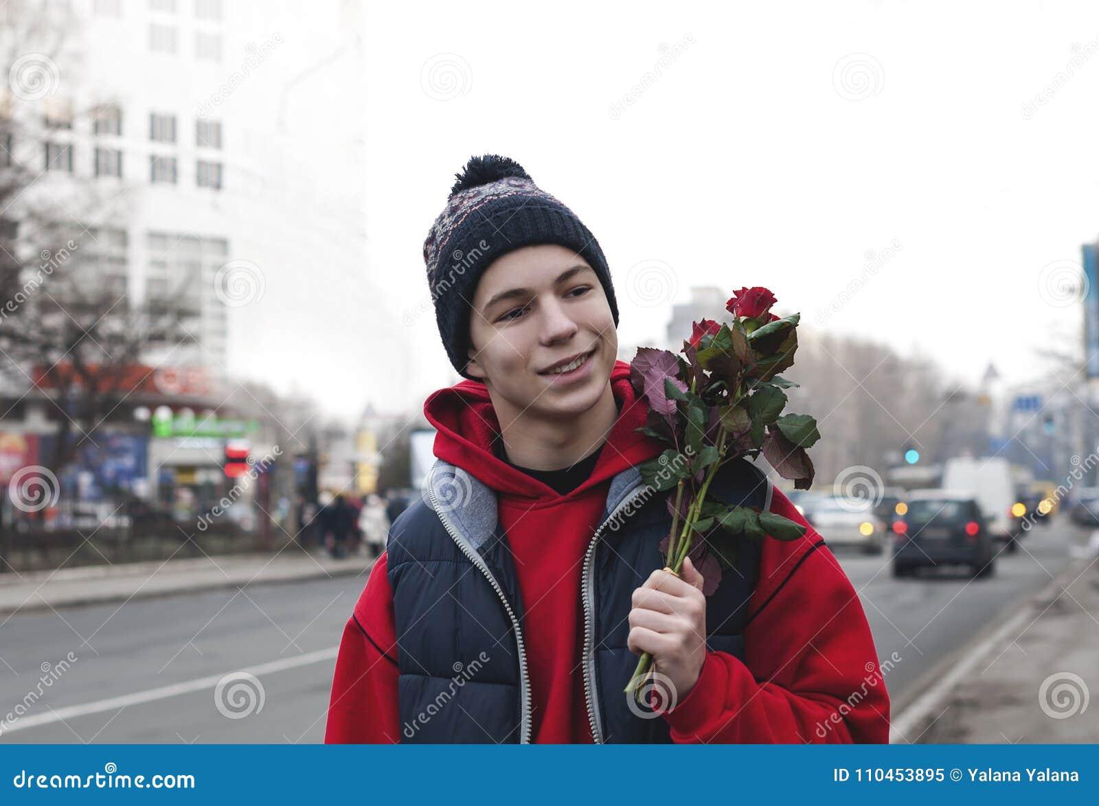 Lycklig ung man med en bukett av rosor på en stadsgata