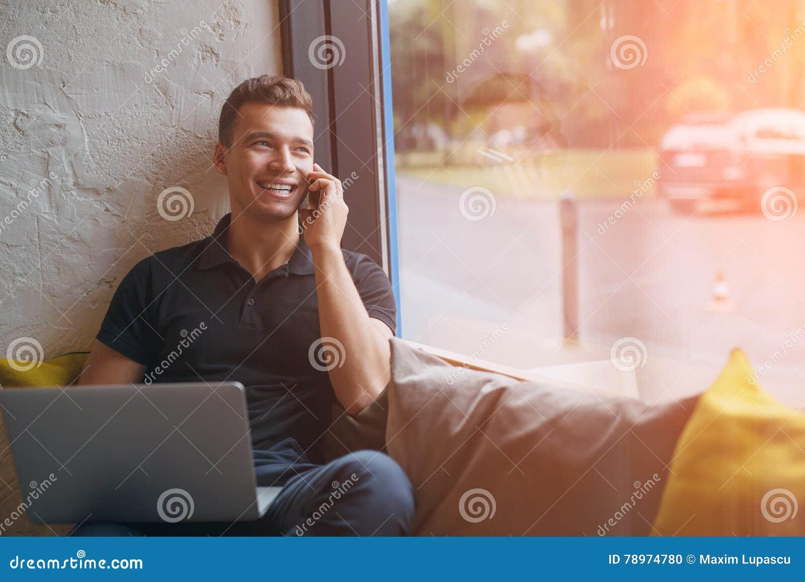 Lycklig ung man som använder bärbara datorn och mobiltelefonen på soffan