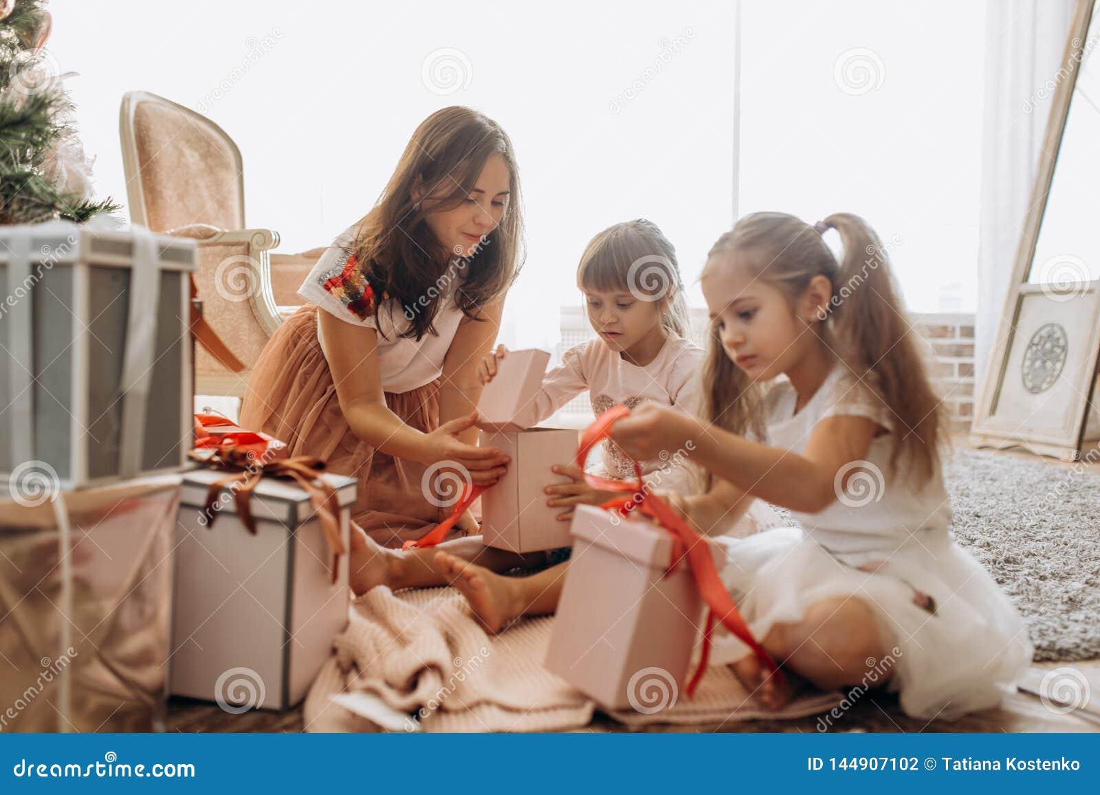 Lycklig ung moder och hennes två charma döttrar i trevlig dresse