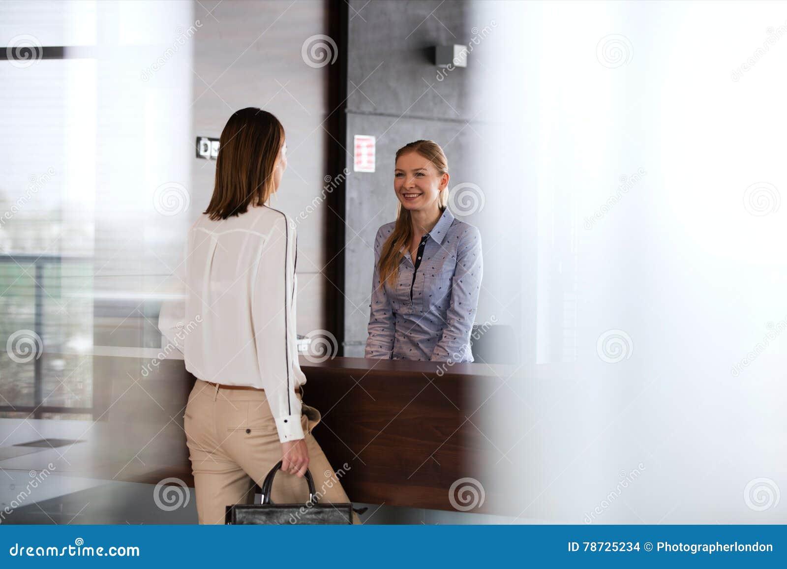 Lycklig ung receptionist som i regeringsställning talar med affärskvinnan