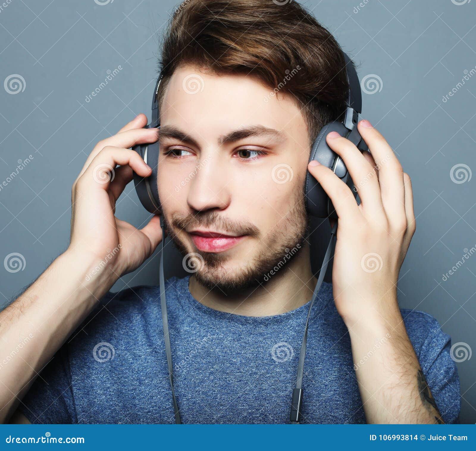 Lycklig ung stilfull man som justerar hans hörlurarannons som ler wh