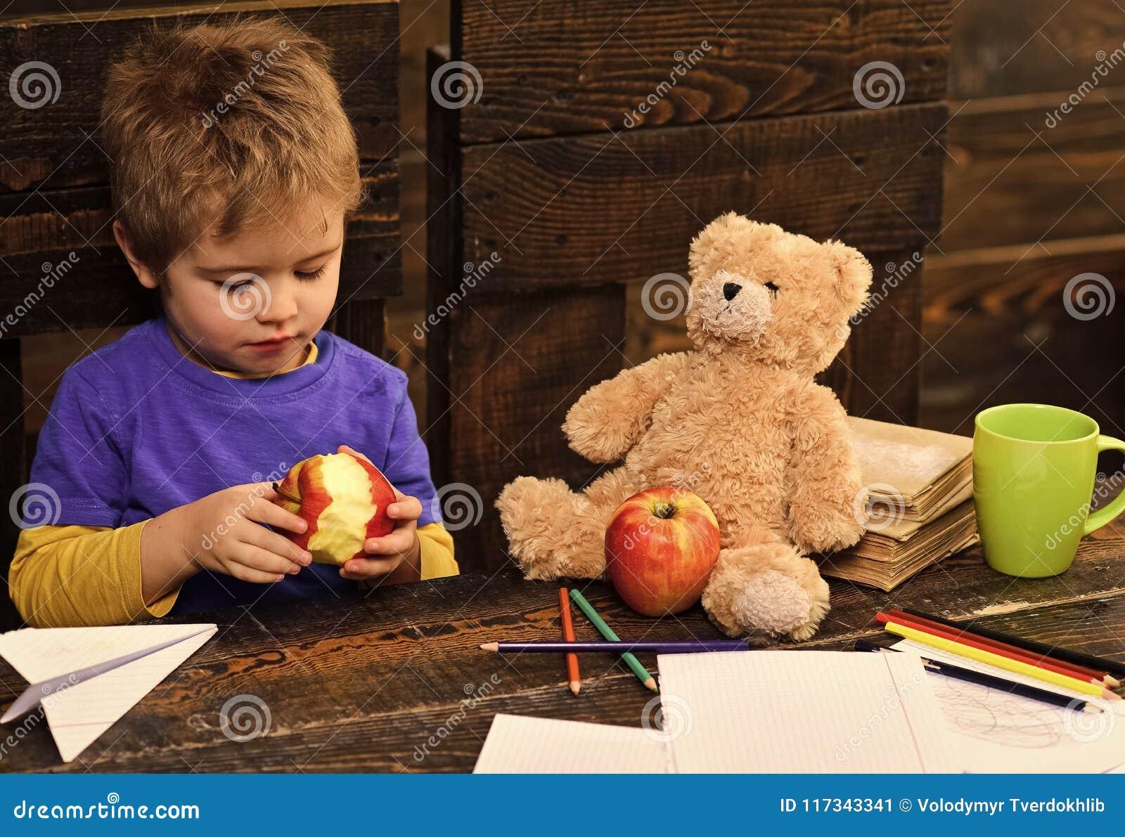 Lycklig unge som har gyckel Förtjusande pojke som äter det läckra äpplet Unge som delar mellanmålet med den favorit- leksaken Ele