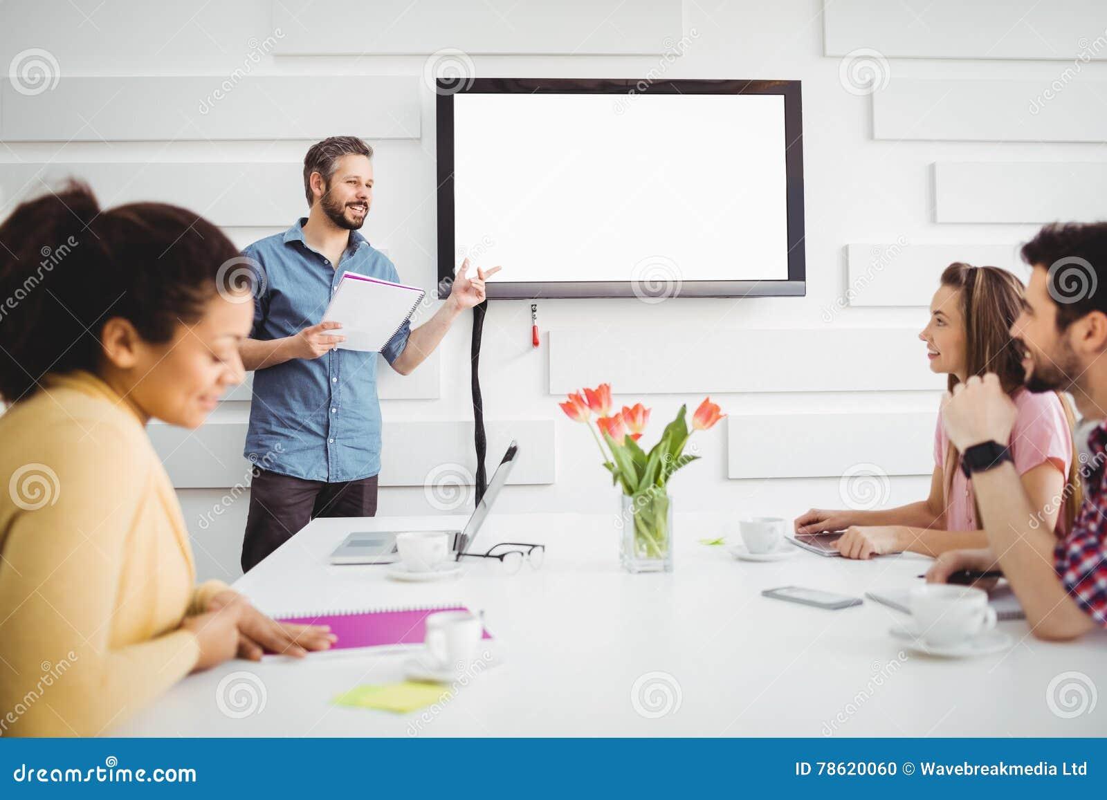 Lycklig utövande geende presentation till kollegor i mötesrum på det idérika kontoret
