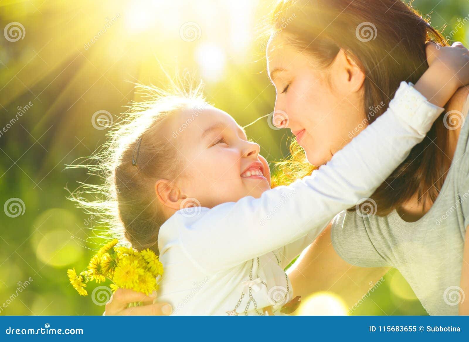 Lycklig utomhus- moder och hennes liten dotter Mamman och dottern som tycker om naturen i gräsplan, parkerar tillsammans