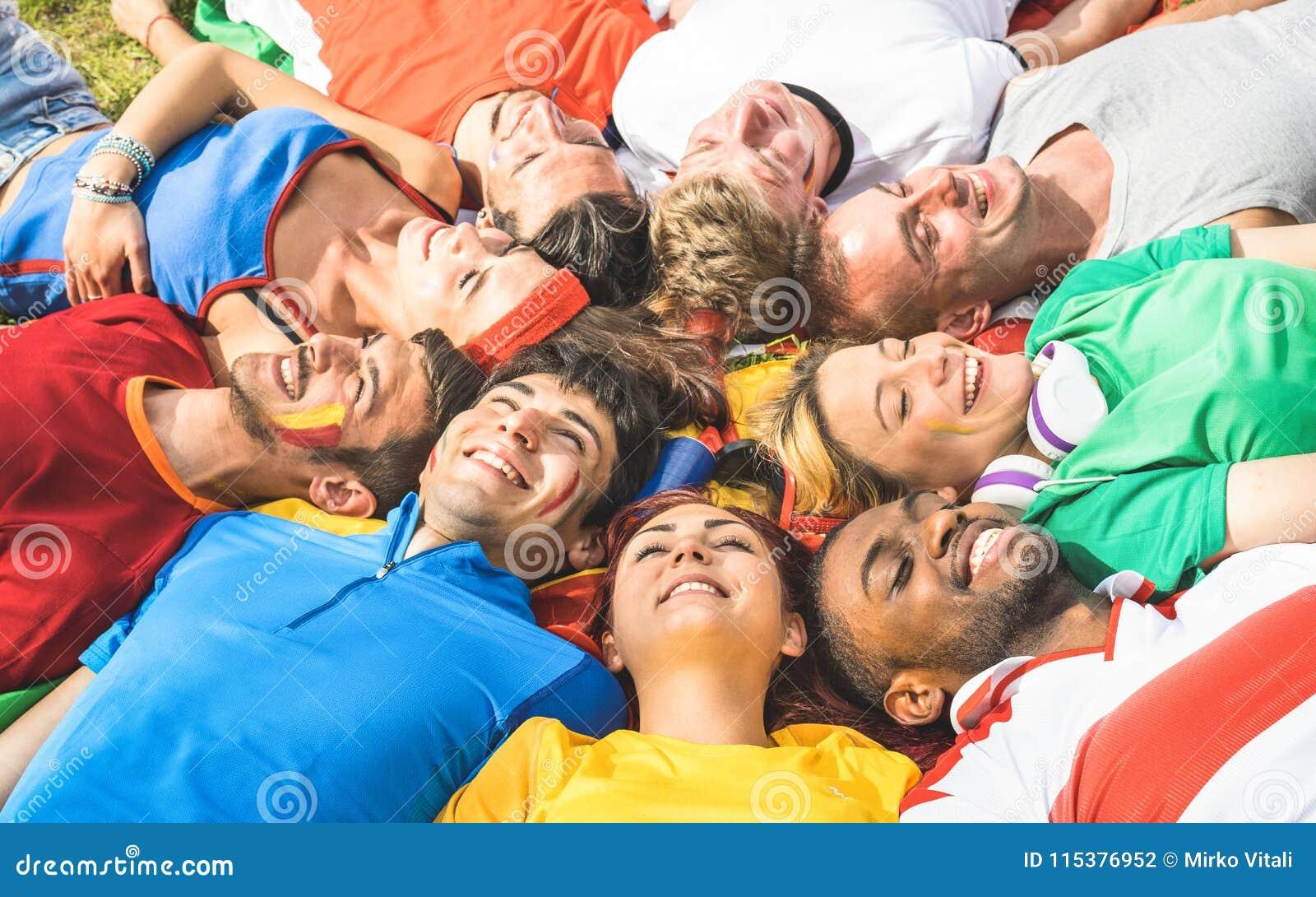 Lycklig vängrupp som ligger på äng efter världsfotbollhändelsen - Fr