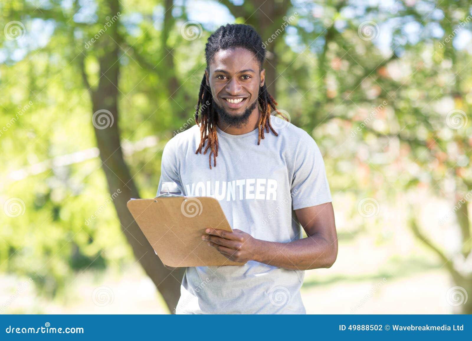 Lycklig volontär i den hållande skrivplattan för parkera
