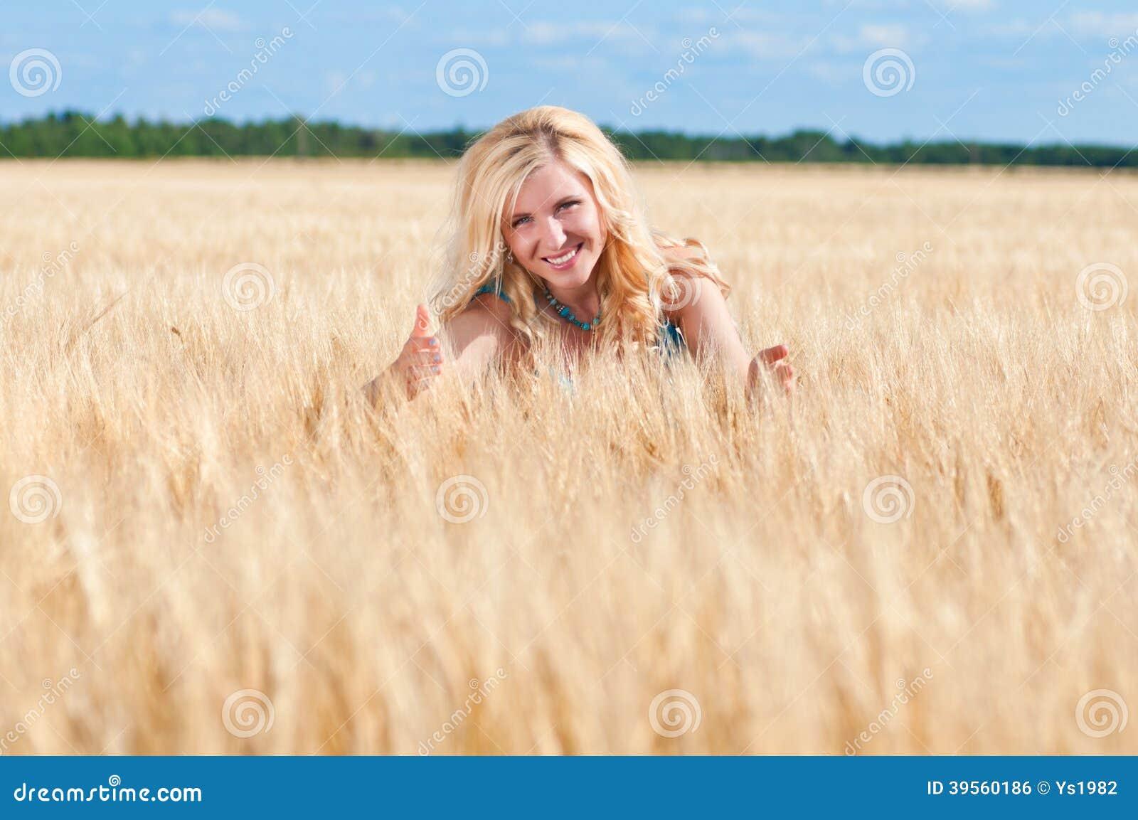 Lycklig womaninblåttklänning i guld- vete