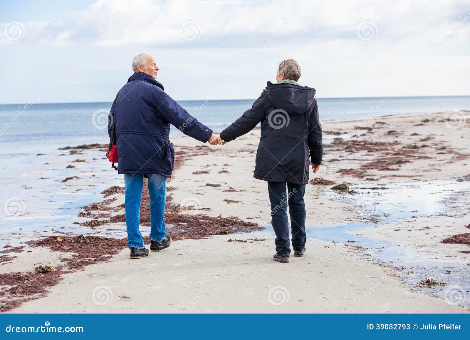 Lyckliga äldre höga par som går på stranden