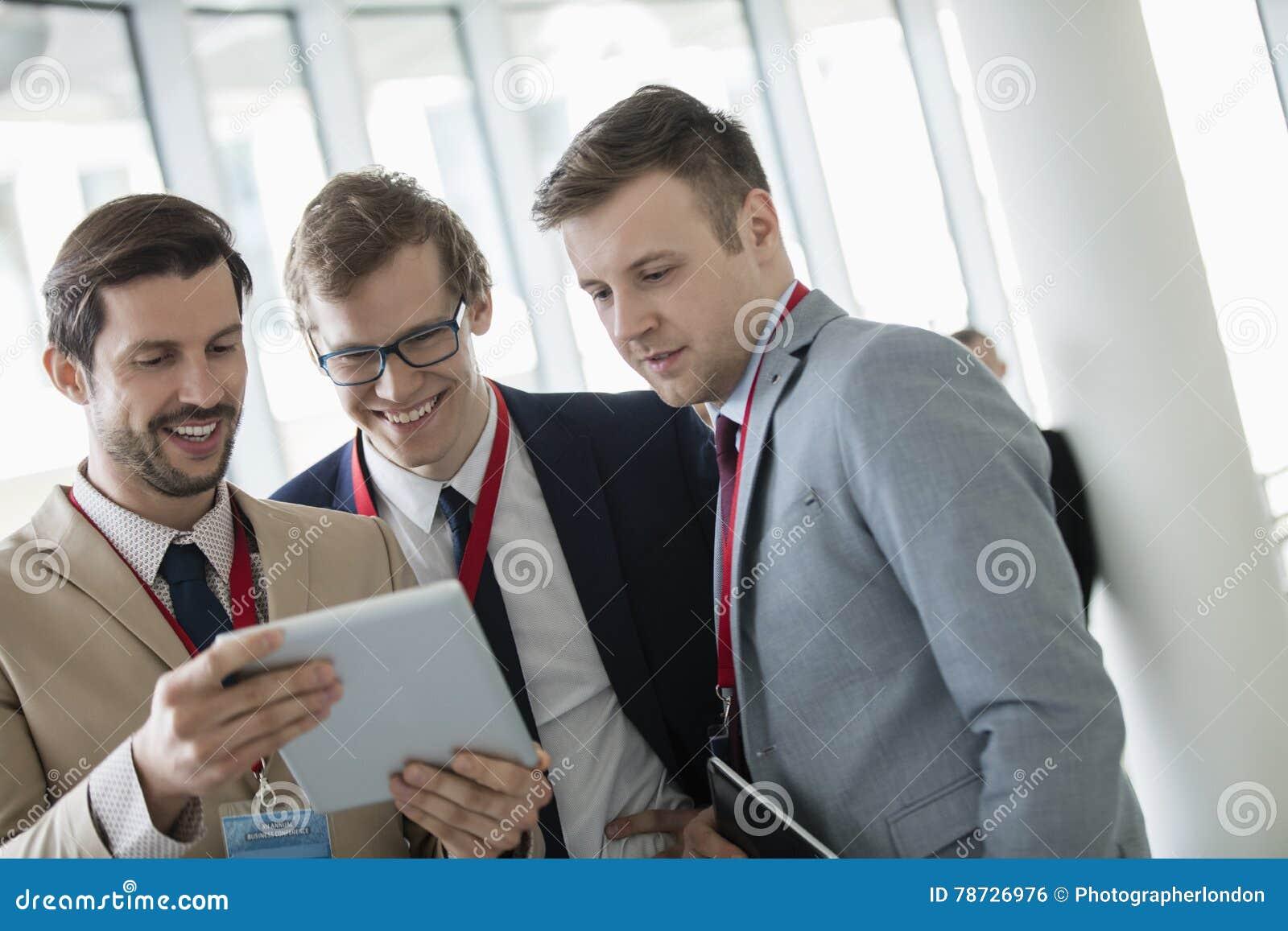 Lyckliga affärsmän som använder den digitala minnestavlan på konventcentret