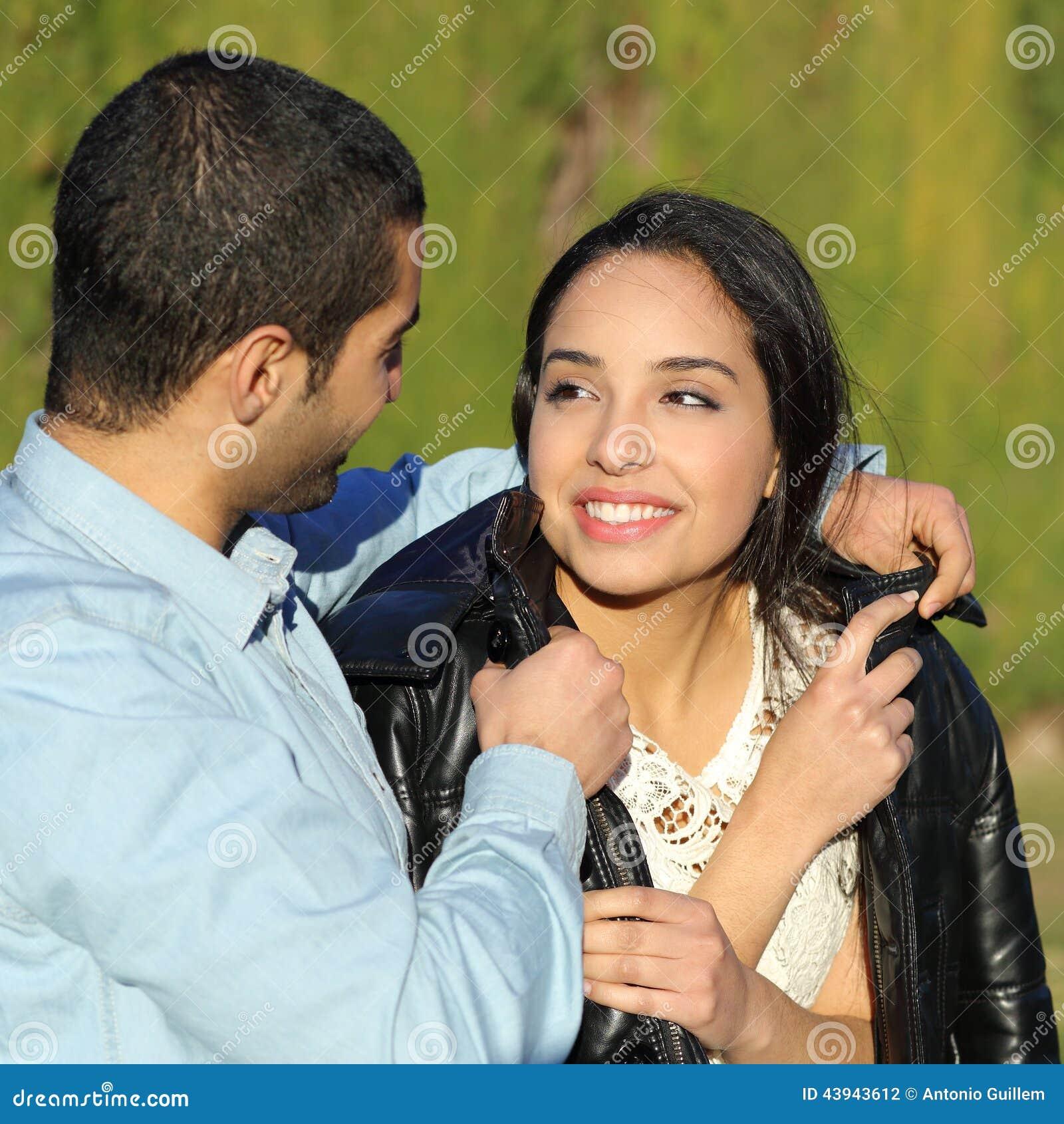 Lyckliga arabiska par som flörtar, medan mannen täcker henne med hans omslag i en parkera