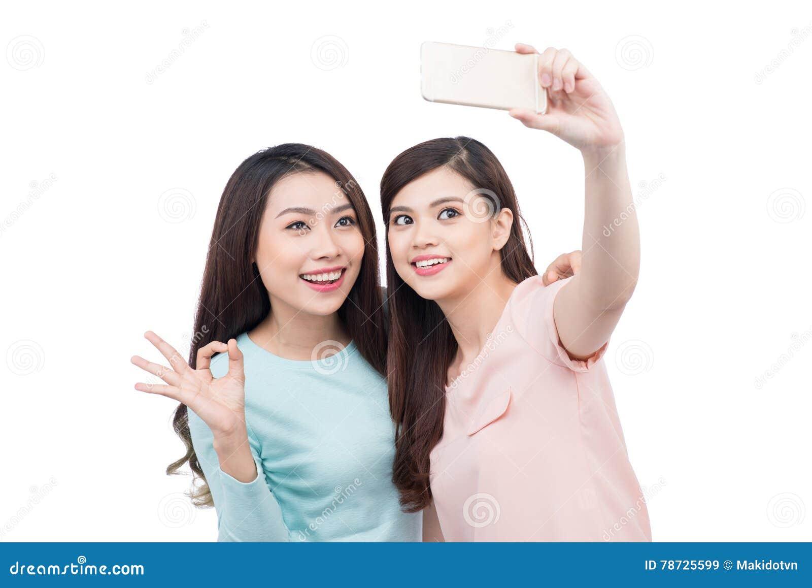 Lyckliga asiatiska kvinnavänner som tar en självstående med en cellpho